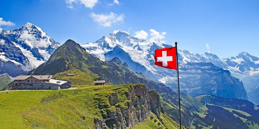 Bandera de suiza con paisaje de montañas y casas